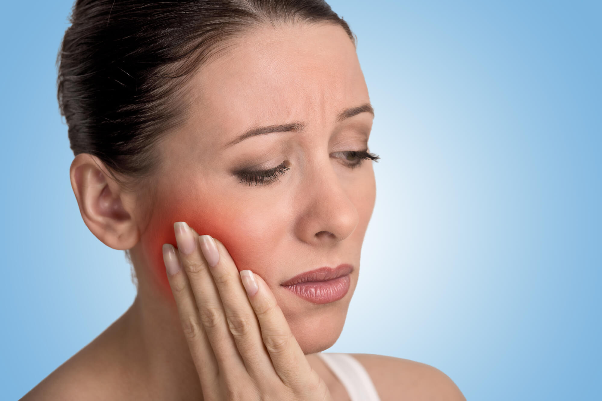 woman touching her face because of toothache needing a root canal therapy in 23233